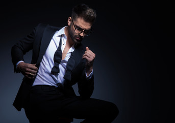 sexy man in tuxedo holds collar while sitting and looking down on grey studio background