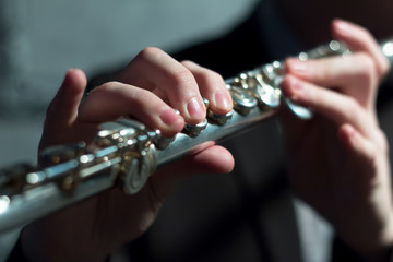 Men's hands on a wind musical instrument. Playing the flute. Shallow depth of field. Music and sound. Modeling light.