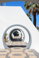 Round archways to bars and shops along the edge of the marina, Vilamoura, Algarve, Portugal.