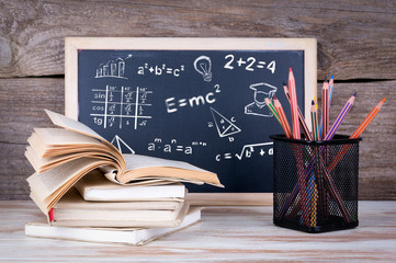math formulas, education and knowledge concept. Stack of books and chalk blackboard on the wooden table.
