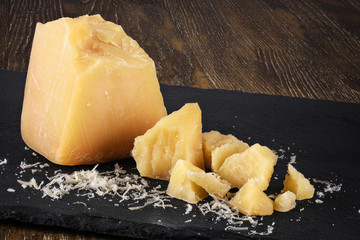 Pieces of parmesan cheese on a dark background.
