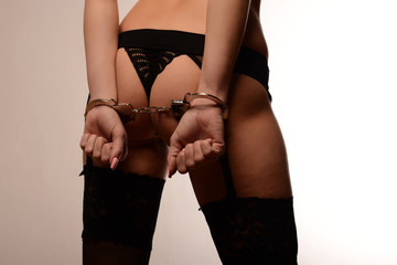 Close-up of beautiful woman's buttom on white. Hands woman with handcuffs. Sado-masochism.