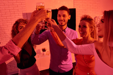 Group of happy young people raising glasses and toasting while celebrating holiday during house party lit by dim red light