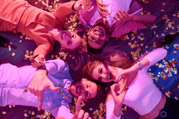 Top view at group of  happy young people gesturing hearts and thumbs up lying on floor among confetti and looking at camera during awesome house party.