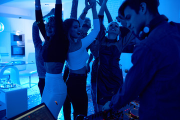Group of modern young people dancing listening to DJ playing music at private house party, focus on beautiful girls lit by blue light