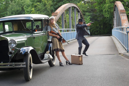 Two models get dressed up in 1930's style  vintage fashion clothes and act the role of  the gangster duo Bonnie and Clyde.