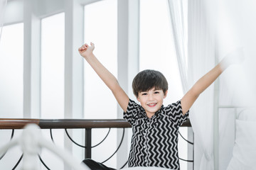 lazy boy kid happy waking up in the white bed rising hands to window in the morning with fresh feeling relax