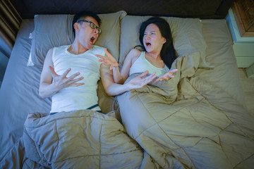 Angry Asian couple fighting on bed at night