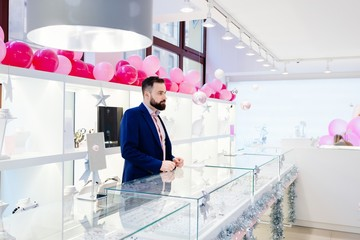 Attractive man with a beard is standing behind the counter