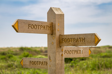 All roads lead to Rome - Sign: Footpath, pointing in all directions, seen in Tide Mills near Seaford, East Sussex, UK