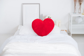 Close up red heart pillow lying on white bed in bedroom.Love valentine honeymoon concept.