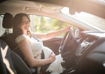 Beautiful smiling pregnant woman sitting in car