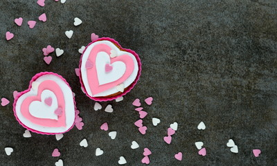 HEART-SHAPED CUPCAKES on stone background with heart confetti