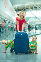 Leisure at the airport.The family is waiting for its flight.Two brothers play,hiding behind a large suitcase.