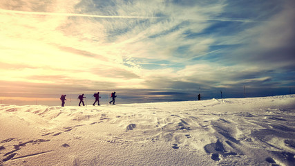 Fototapeta Winter mountain landscape with travelers silhouettes at sunset, color toned picture. obraz