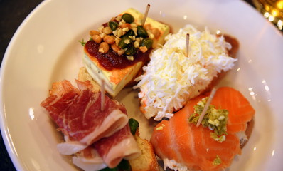 Leckere Tapas mit Lachs, Käse, Tintenfischsalat und Schinken auf einem weißen Teller