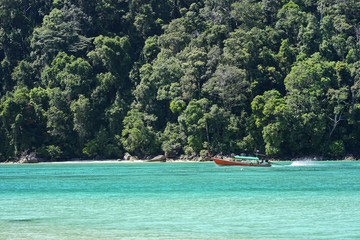 Long-tailed boat in the clear sea at Surin Island in Phang Nga Province, Thailand.