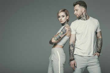 stylish tattooed couple in sportswear posing together, isolated on grey Wall mural