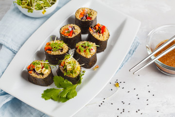 Vegan sushi rolls with quinoa, vegetables and soy-nut sauce on a white plate, light background. Vegan Healthy Food Concept.