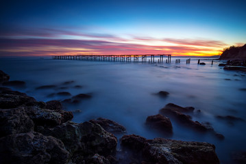 Rocky beach after sunset / Rocky beach long exposure seascape after sunset and a silhouette of a broken bridge