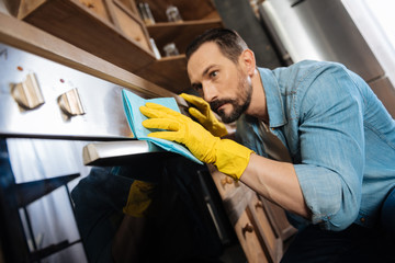 Crystal clean. Earnest musing male cleaner wearing gloves while using cleaning cloth and cleaning oven