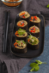 Vegan sushi rolls with quinoa, vegetables and soy-nut sauce on a black plate, black background. Vegan Healthy Food Concept.