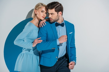 beautiful couple in stylish blue suit and dress standing together in aperture on grey
