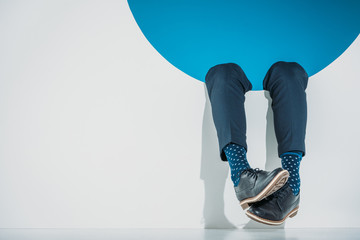 close-up partial view of stylish man falling into hole on grey Wall mural