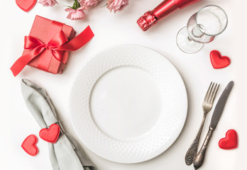 Valentines day dinner with table place setting with red gift, a bottle of champagne, hearts with silverware on white background. View from above. Valentine's card.