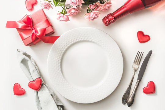 Valentines day dinner with table place setting with red gift, a bottle of champagne, pink roses, hearts with silverware on white. View from above. Valentine's card.