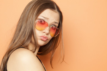 young funny girl with orange sunglasses on orange background