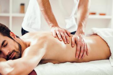 Young man is enjoying massage on spa treatment.