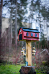 Selectiv focus of red bird feeder house barn with tallow balls. Winter outdoors.