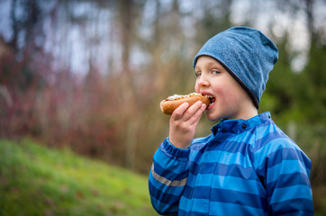 Boy in blue winter rain jacket and hat eating hotdog outdoors, profile view.