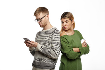 Studio shot of suspicious distrustful young blonde female in green top standing next to her bearded boyfriend, looking over his shoulder, spying over him while he is typing message using mobile phone