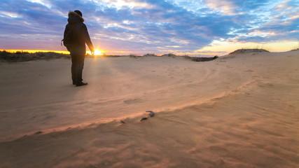 man looking at sunset / sandy desert, late autumn