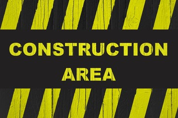 Construction area warning sign with yellow and black stripes painted over cracked wood. Concept image for construction sites meaning: do not enter the area, caution, danger