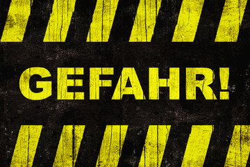 """Gefahr (in German, """"danger"""") text warning sign with yellow and black stripes painted over grungy cracked wood."""