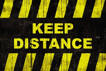 """Grungy """"keep distance"""" text warning sign with yellow and black stripes painted over cracked wood."""