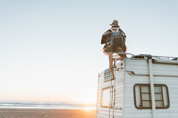 Charming young woman with hat, poncho,  backpack standing on roof of recreational vehicle on the ocean beach at sunset.