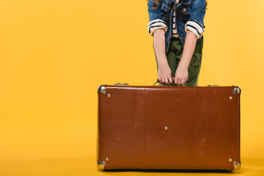 partial view of child holding leather suitcase isolated on yellow