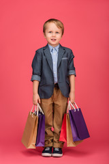 cute little boy with shopping bags in hands isolated on pink