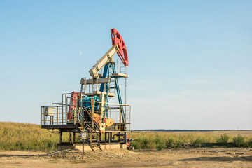Pumping unit is working in oil field on the green field background