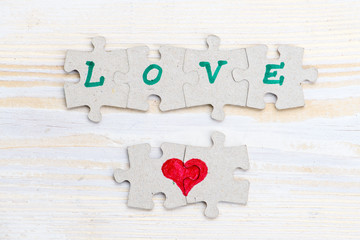 Word Love and heart made of pieces of jigsaw puzzle on light wooden table, close-up