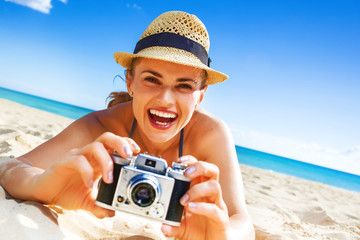 happy healthy woman on beach taking photo with digital camera
