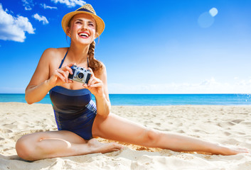 happy active woman on seashore taking photo with digital camera