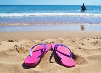 pink flip flops at a greek beach - greek summer destination