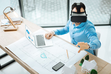 Concentrated on work. The top view of a pleasant young man working on the laptop and using a VR headset, visualizing the constructions