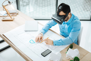 Dedicated worker. The top view of a bristled young man sitting at the work desk and creating a blueprint while wearing a VR headset