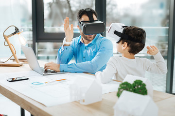 Nice team. Pleasant young architect in VR headset sitting at his desk in the office next to his little son and giving him a high-five while the boy wearing a VR headset too